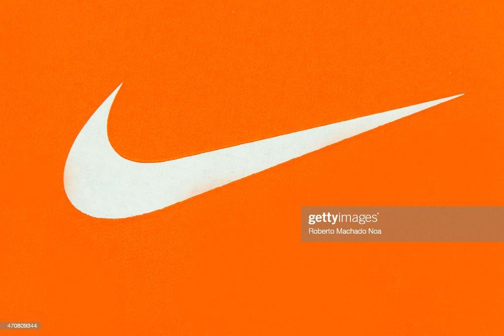 White Nike Logo on Orange Background;Nike, Inc. is an ...