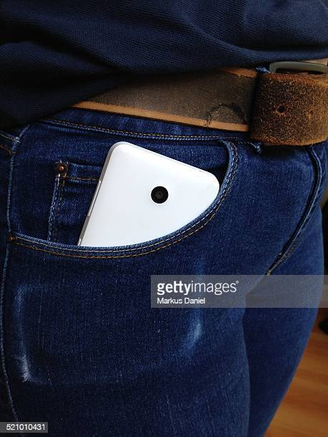 A white Nokia lumia in a woman's blue jeans with leather belt front pocket