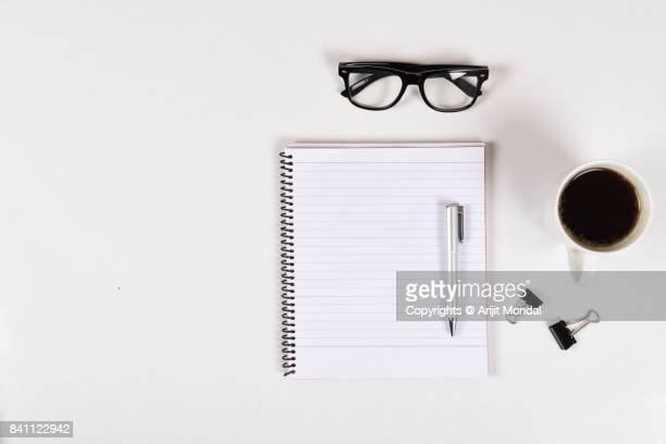 White office desk of many things eyeglasses, notebook, coffee, pen with copy space