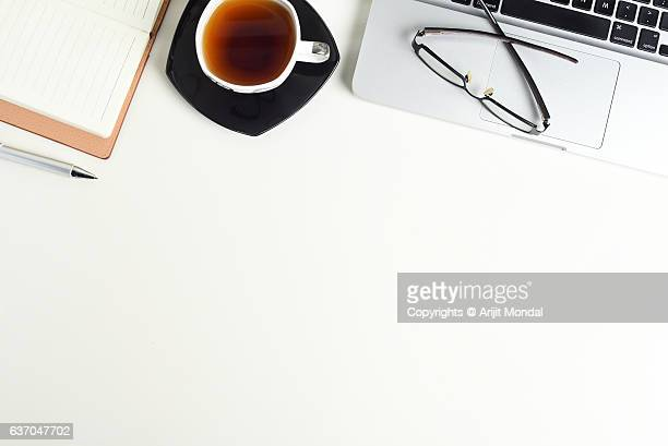 White office desk table with a Laptop, Notebook, cup of tea and eye glasses on it, top view with copy space.