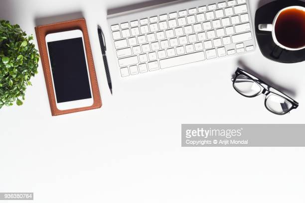 White Office Desk Table With Smartphone And A Lot Of Things Top View With Copy Space