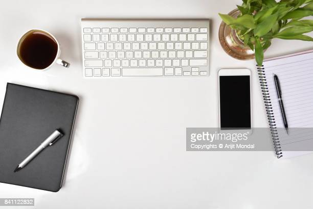 White office table top view with smart phone, computer keyboard copy space