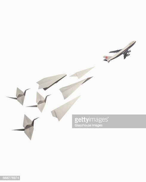 White Origami Cranes Flying with an Airplanes
