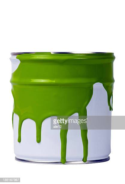 White paint can with green paint spilling out the top