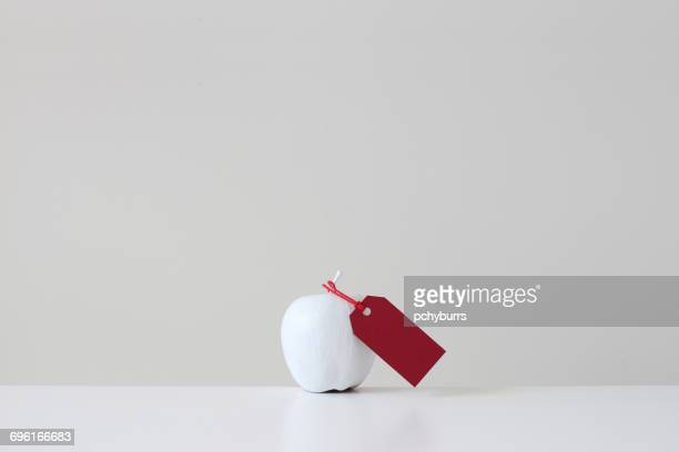 White painted apple with red tag