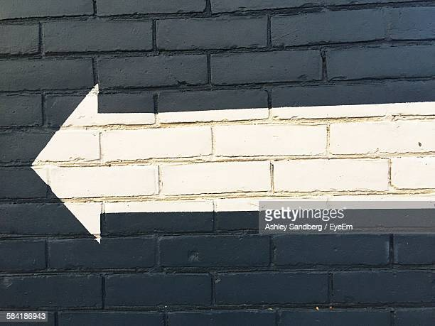 White Painted Arrow Symbol On Black Brick Wall