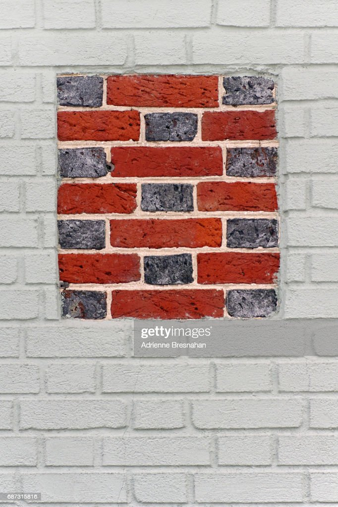 White Painted Brick Wall With Squre Of Blue And Bricks In The Center Stock