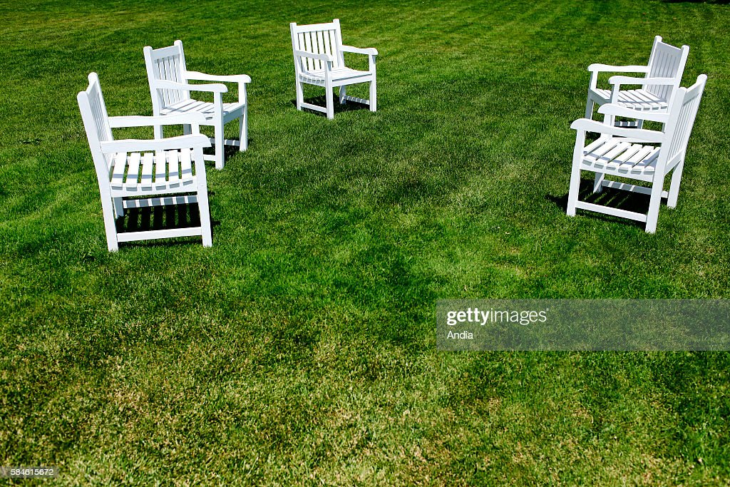 White painted wooden garden chairs on a freshly cut lawn ...