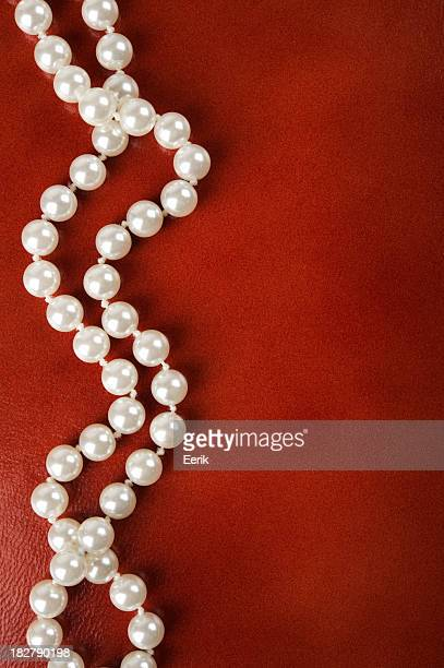 White pearl necklace on a red background