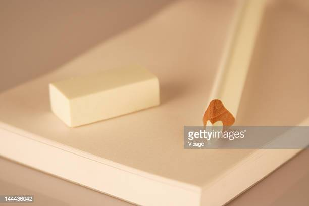 A white pencil, papers and eraser