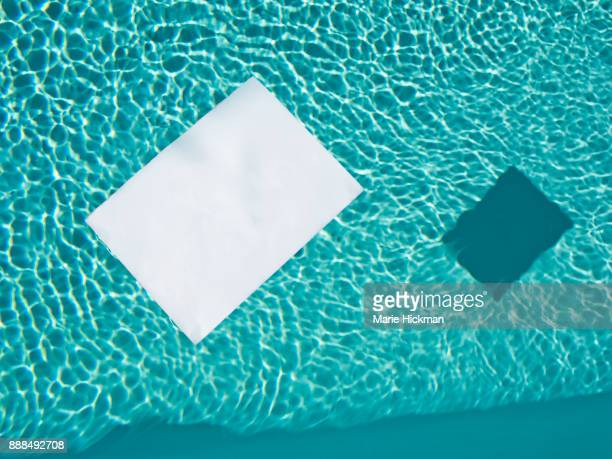 'FILL IN THE BLANK'. White piece of paper floating in a pool.