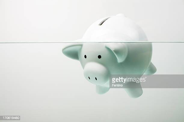 white piggy bank sinking in water - evil stock pictures, royalty-free photos & images