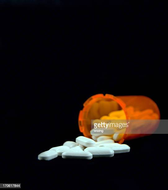 white pills and yellow bottle spilled  on black - anti depressant stock pictures, royalty-free photos & images
