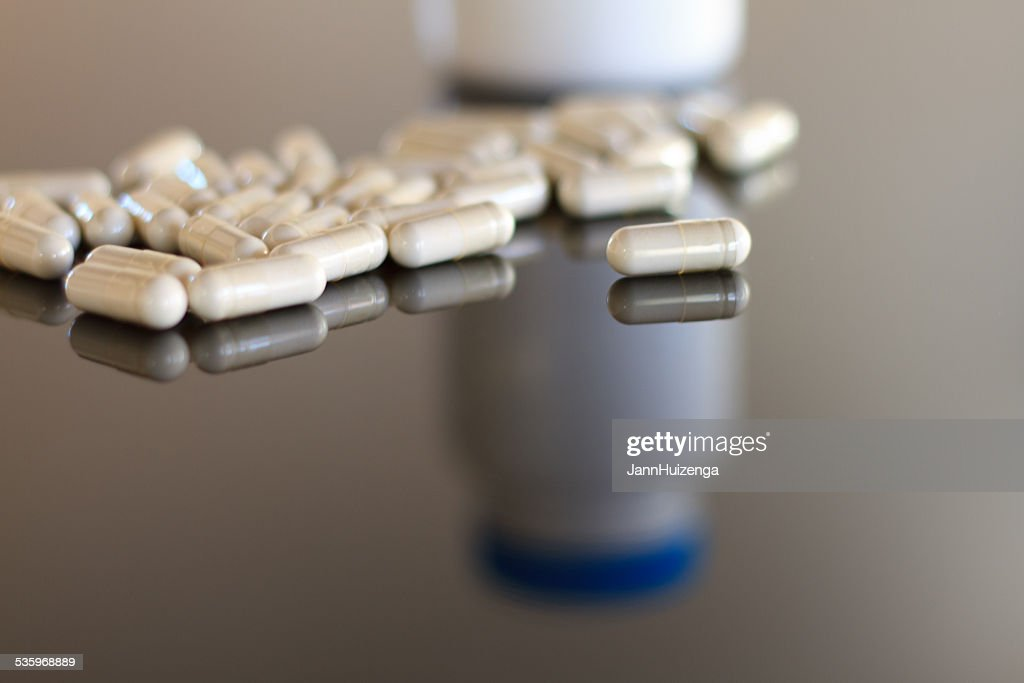 White Pills on Gray (Reflective) Background : Stock Photo