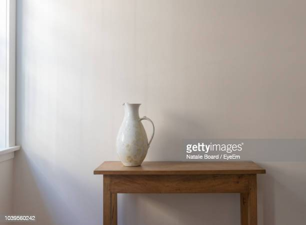white pitcher on table against wall at home - naturaleza muerta fotografías e imágenes de stock
