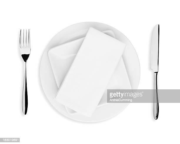 Weiße Serviette, Teller, Messer und Gabel auf weißem Hintergrund