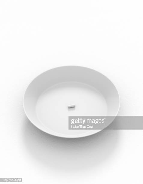 a white plate on a clean white surface with a single solitary white pill - atomic imagery stock pictures, royalty-free photos & images