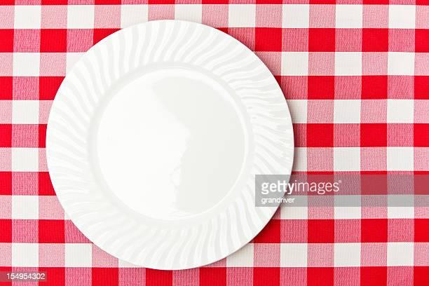 Weißen Teller auf rote Tischdecke Gingan-Karomuster