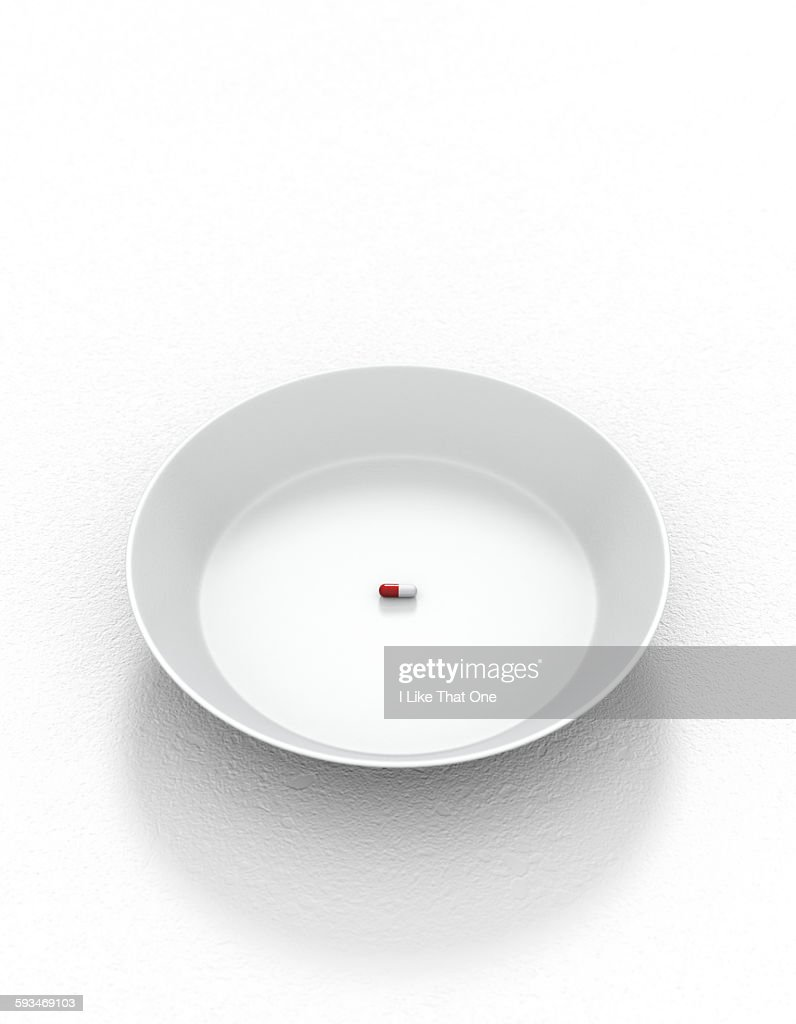White plate & solo pill resting on white surface : Stock Photo