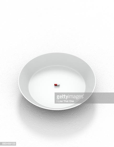 White plate & solo pill resting on white surface