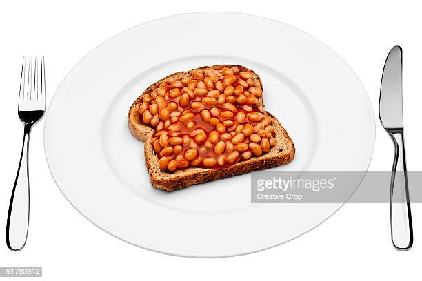 White plate, steal knife and fork baked beans on t