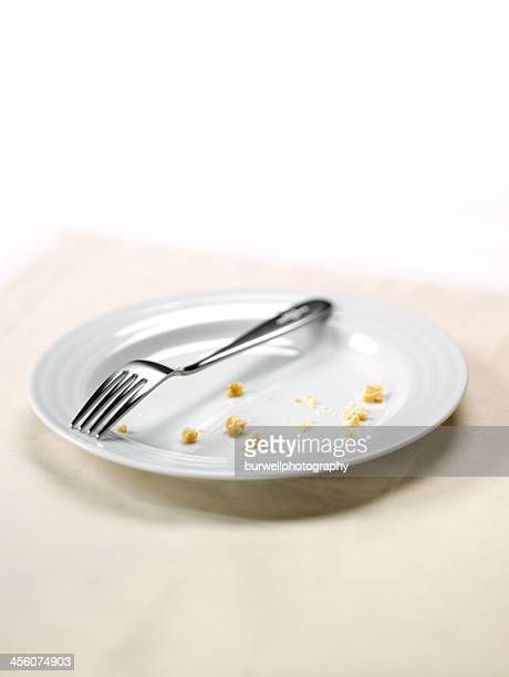 White plate with crumbs and fork