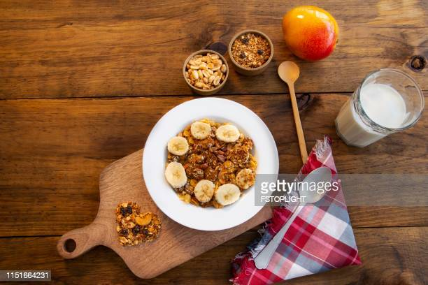 White plate with granola and slices of banana