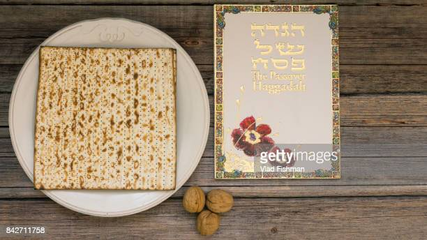 White plate  with matzah or matza and Passover Haggadah on a vintage wood background presented as a Passover seder feast or meal with copy space