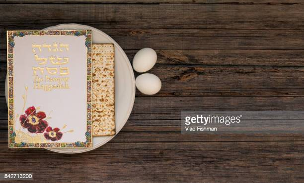 white plate  with matzah or matza and passover haggadah on a vintage wood background presented as a passover seder feast or meal with copy space. - passover seder plate stock pictures, royalty-free photos & images