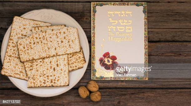 white plate  with matzah or matza and passover haggadah on a vintage wood background presented as a passover seder feast or meal with copy space - happy passover stock pictures, royalty-free photos & images