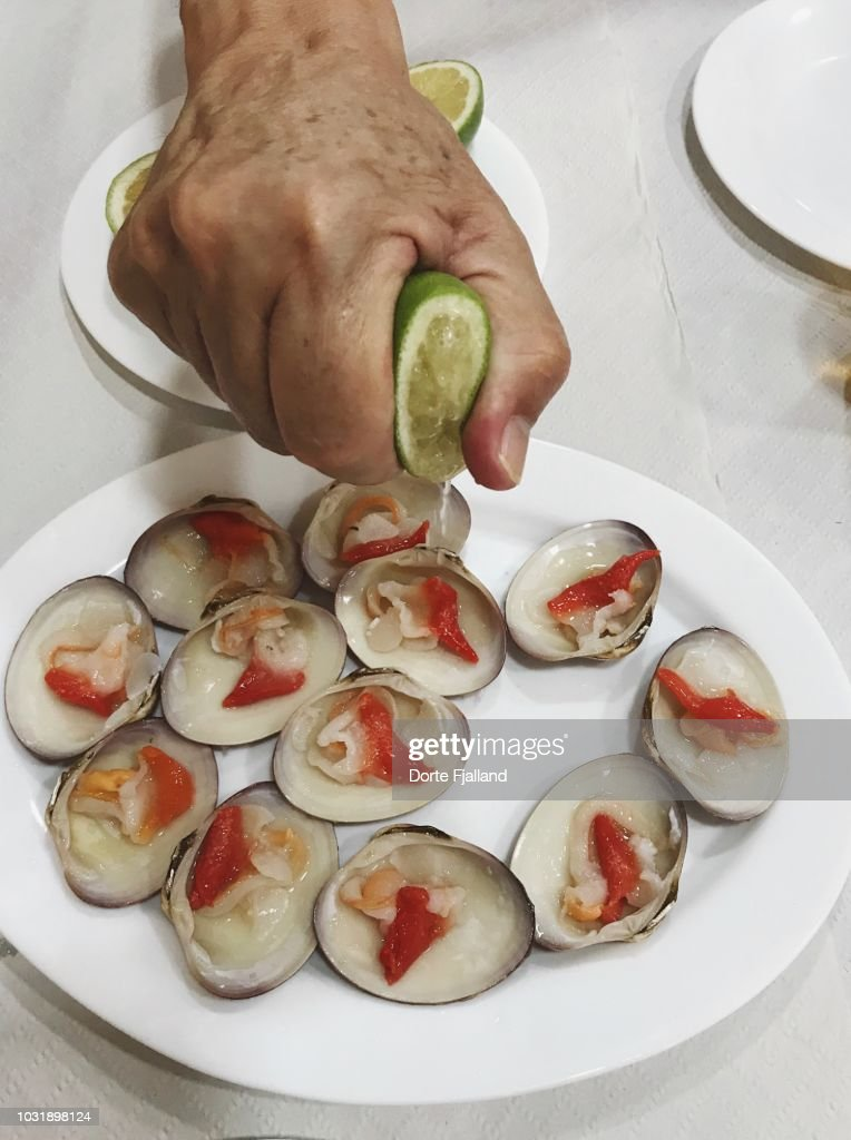 A white plate with raw smooth clams and a hand drizzling them with lemon juice : Foto de stock