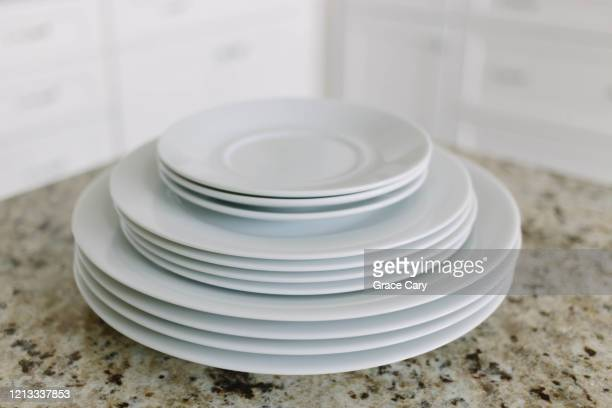 white plates and saucers on kitchen counter - 積み重ねる ストックフォトと画像