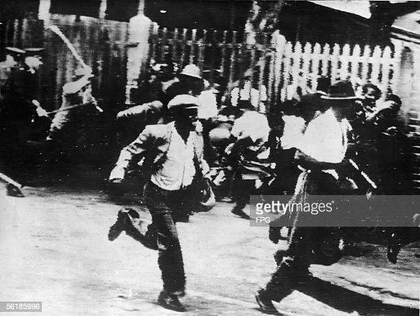 White policemen charge into a racialy motivated conflict between African and Indian residents Durban South Africa January 17 1949 Over 140 people...