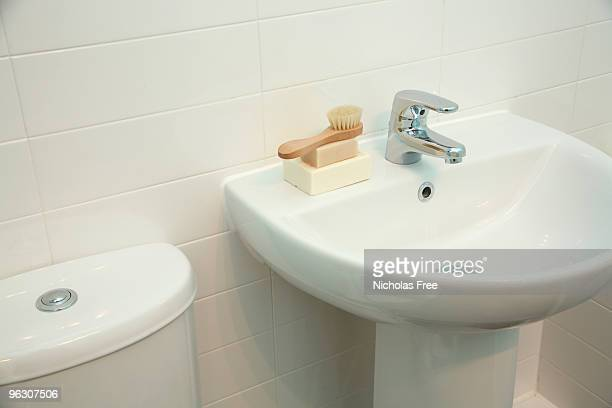 White, porcelain bathroom sink with soap and brush on ledge