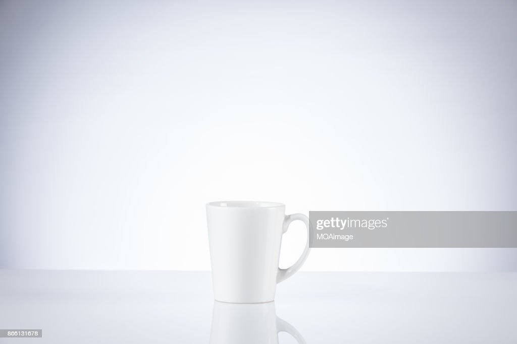 A white porcelain cup on a table indoors : Stock Photo
