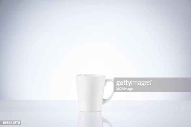 A white porcelain cup on a table indoors