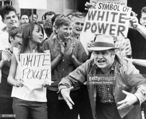 White power supporters gesture at civil rights marchers passing by in Gage Park Chicago Illinois August 15 1966