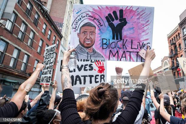 A white protester carries a sign with a drawing of George Floyd a black fist in the air and the words Black Lives Matter and Justice for George Floyd...