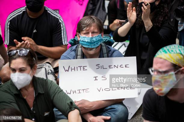 "White protester holds a sign that says, ""White Silence is White Violence"" while sitting with others in the large crowd that gathered in Foley Square...."