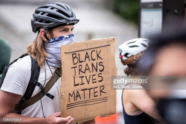 A white protester wearing a mask holds a sign that says BLACK TRANS LIVES MATTER among the large crowd in Foley Square Protesters took to the streets...