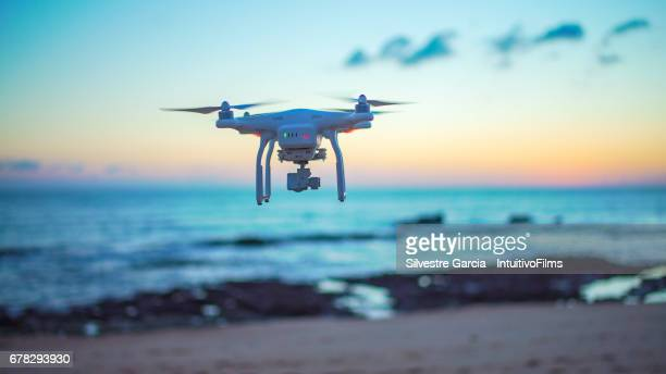 a white quadcopter drone flies at sunset in the beach over the sand - helicopter photos stock pictures, royalty-free photos & images