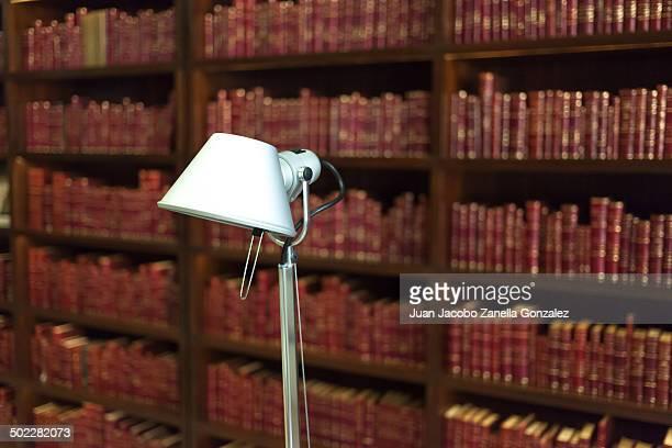 White reading lamp stands against red bookshelves.