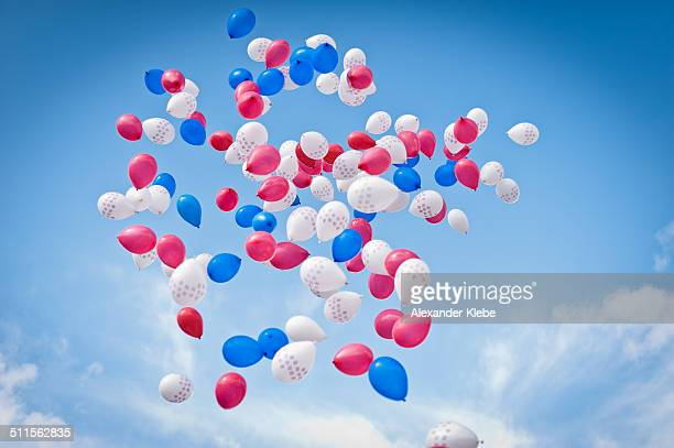 White, red and blue balloons in the air