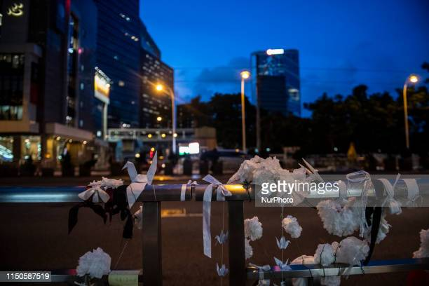 White ribbons are tide to a fence in Honor of a man who died after falling from a scaffolding in Pacific Place while protesting demanding the...