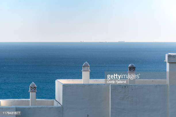 white roof tops in the foreground with the blue sea, a few ships and the blue sky in the background - dorte fjalland fotografías e imágenes de stock