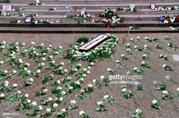 White roses are displayed on the ground along a golden crack part of the memorial for the victims of last year's deadly truck attack at the Christmas...