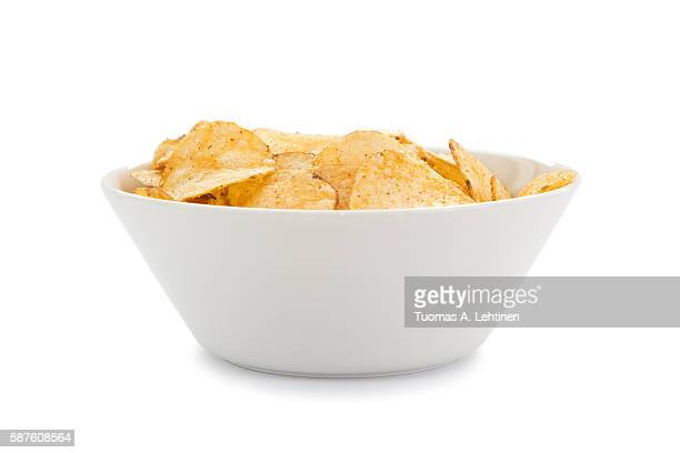 White round bowl full of potato chips viewed from the front, isolated on white background.