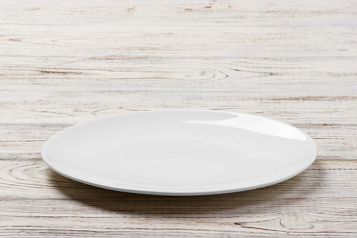 White Round Plate on white wooden table background. Perspective view 913055738