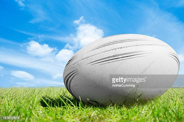 White rugby ball on green grass under blue sky