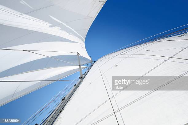 White sails against blue sky seen from below